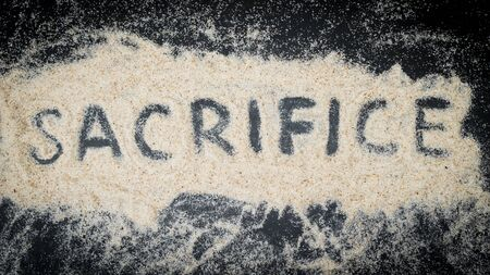 Flat lay of SACRIFICE word written on white sand with black wooden background Stock Photo