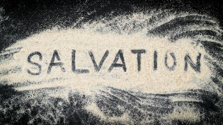 Flat lay of SALVATION word written on white sand with black wooden background