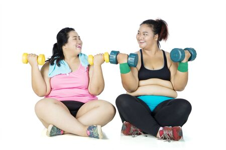 Two overweight women exercising with dumbbells while sitting in the studio, isolated on white background