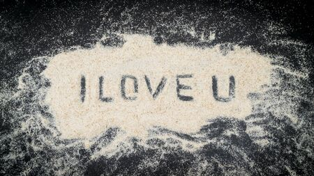 I LOVE U text written on white sand with black wooden background