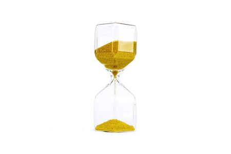 Transparent sandglass with golden sand in the studio, isolated on white background