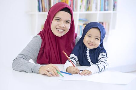 Beautiful muslim mother and daughter studying at home
