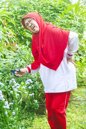 Senior muslim woman having backache during gardening in the backyard garden