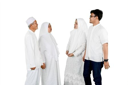 Parents with son and daughter gathering together for Eid Mubarak celebration isolated over white