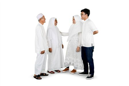Parents with son and in-law gathering together for Eid Mubarak celebration isolated over white