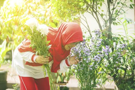Attractive senior muslim woman kissing flowers in the backyard garden
