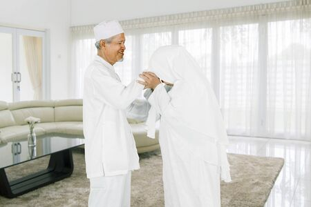 Eid Mubarak celebration concept: Wife shaking hand and asking for forgiveness to her husband at home