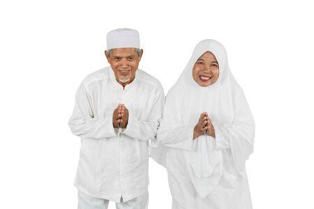 Old Muslim couple showing greeting gesture together during Eid Mubarak celebration isolated over white background