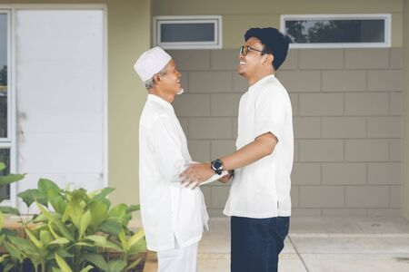 Muslim father greets son arriving at the house for Eid Mubarak celebration