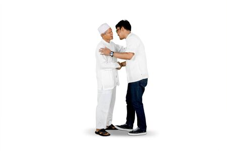 Eid Mubarak celebration concept: son shaking hand and asking for forgiveness to father isolated over white background