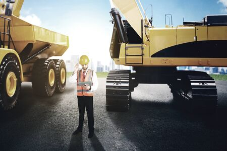 Male engineer working with a digital tablet while standing at construction site with excavator and truck background Banco de Imagens