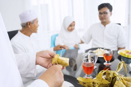 Hands cutting a ketupat while happy family talking at the blurred background in their dining room