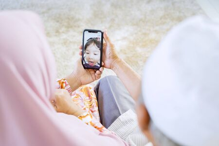 Elderly Asian muslim couple holding a phone, while video calling their adorable granddaughter in their home