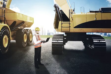 Male engineer working with laptop while standing at construction site with excavator and truck background