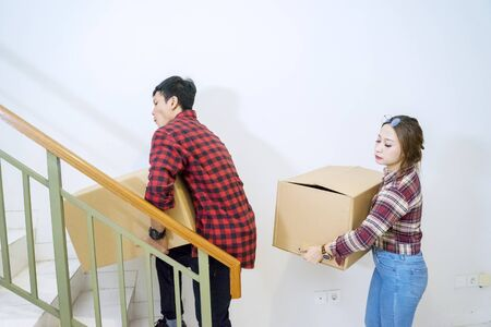 Young couple moving house and carrying cardboard in their new house Banque d'images - 143515191
