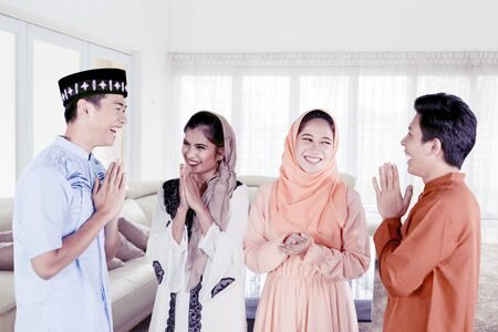 Group of happy young muslim people greeting to each other at home
