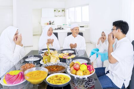 Portrait of happy muslim family praying together before eat while celebrating eid mubarak in dining room Stock Photo