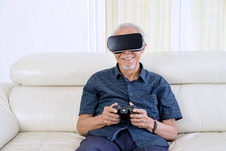 Portrait of old man using virtual reality glasses and joystick while sitting in the living room