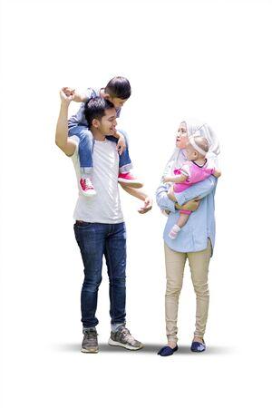 Toute la longueur des parents musulmans et de leurs enfants marchant ensemble dans le studio, isolés sur fond blanc Banque d'images