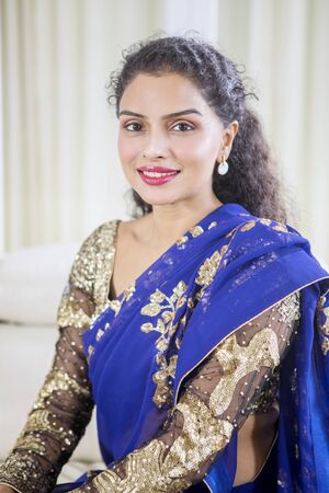 Portrait of pretty woman wearing blue traditional clothes while smiling at camera Imagens