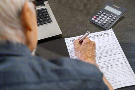 Elderly man filling health insurance form with laptop and calculator on the table at home Standard-Bild