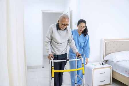 Picture of young nurse helping old man to walk with walker equipment while standing in the bedroom