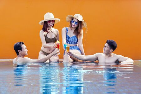 Happy young friends in swimwear making drinks toast on the poolside. Pool party concept