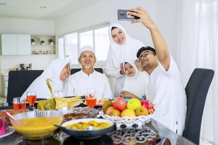 Portrait of muslim family taking selfie picture while smiling and sitting in dining room together
