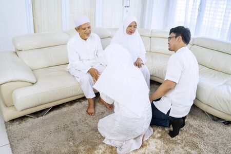 Portrait of young people and old muslim parents forgiving each other while sitting on sofa
