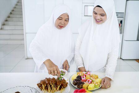 Portrait of muslim mother and her daughter serving food together for celebrating eid mubarak Imagens
