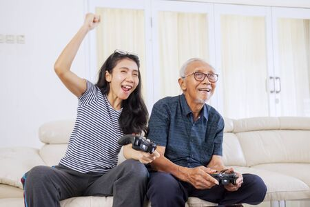 Portrait of beautiful Asian woman cheering & clenching her hand while playing video games along with his old father on the sofa in their living room