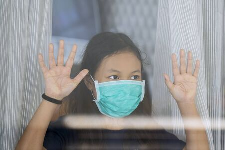 Portrait of cute girl wearing medical mask and looking through outside the window