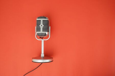 Flat layout of a condenser microphone with its wire, isolated in red background Archivio Fotografico
