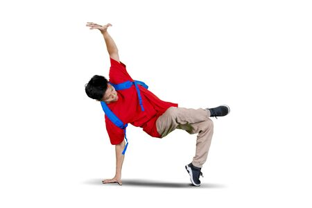 Picture of college student doing break dance in studio while wearing backpack, isolated on white background