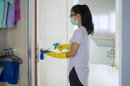Portrait of young female using disinfectant to clean the door while wearing gloves