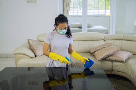 Portrait of young woman cleaning the table using disinfectant liquid while wearing gloves Standard-Bild