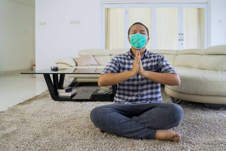 Portrait of asian man doing meditation at home while wearing face mask and sitting on the mat