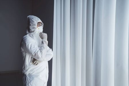Portrait of man wearing hazmat suit, while daydreaming in some dark room of hospital