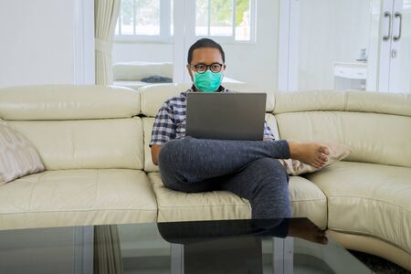 Portrait of businessman working at home using laptop while wearing face mask during coronavirus outbreak