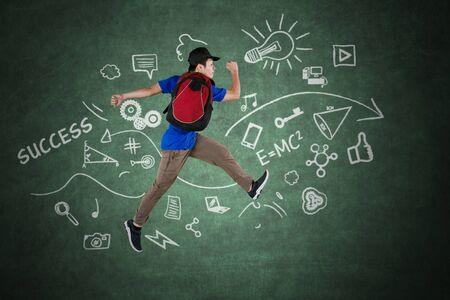 Picture of male university student jumping with doodles on the blackboard while carrying backpack