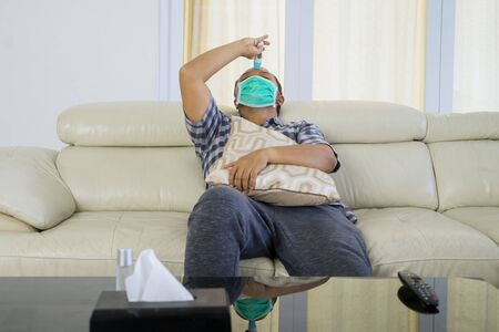 Portrait of young man using thermometer to check his temperature while wearing face mask at home