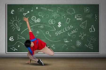 Picture of university student doing handstand in the classroom while carrying backpack with doodles on the blackboard