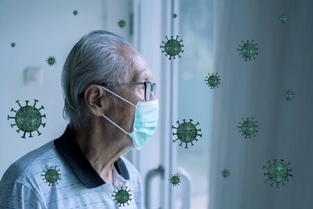 Portrait of old man looking through the window while wearing face mask to prevent from coronavirus