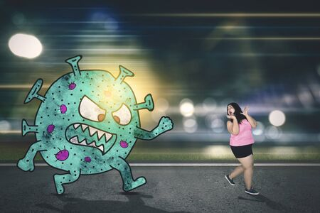 Scared young woman in sportswear chased by Coronavirus and running on the road