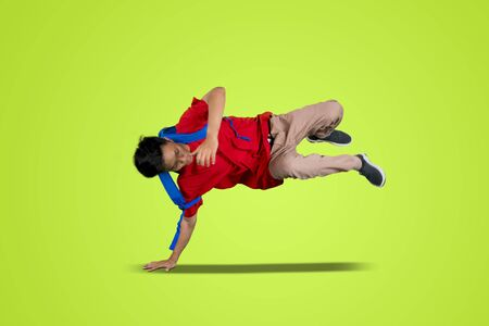Attractive bboy break dancing in the studio while carrying backpack with green background
