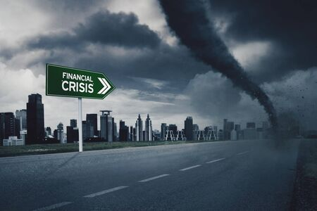 Dark violent tornado at the end of the road with financial crisis sign