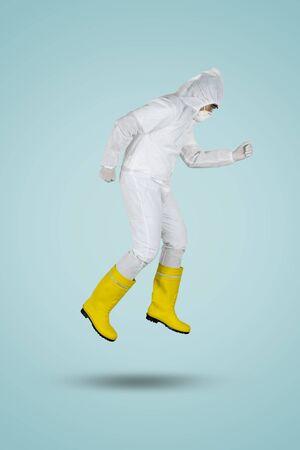 Doctor in hazmat suit and mask running in studio. Coronavirus outbreak concept 版權商用圖片
