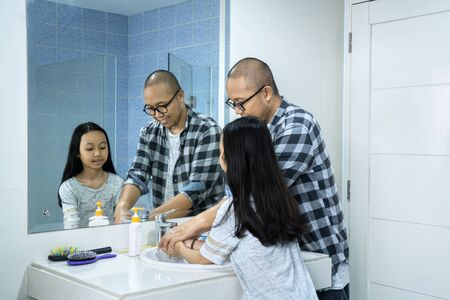 Young man and his daughter washing hands with a soap under flowing water on sink for coronavirus spread prevention. Shot in 4K resolution