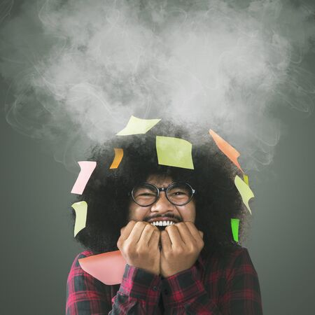 Anxious Afro man biting nails with blank sticky notes and smoke over his head