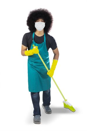 Male janitor wearing a medical mask to prevention coronavirus while holding a broom in the studio. Isolated on white background